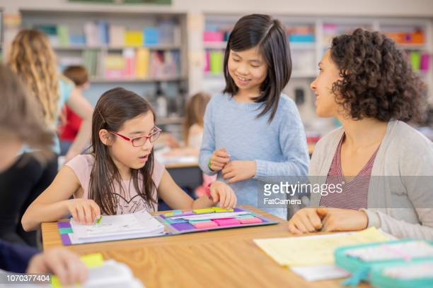 teacher helping 4th graders in her classroom - learning objectives stock pictures, royalty-free photos & images