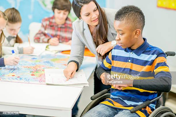 Teacher Helping a Disabled Student with an Assignment