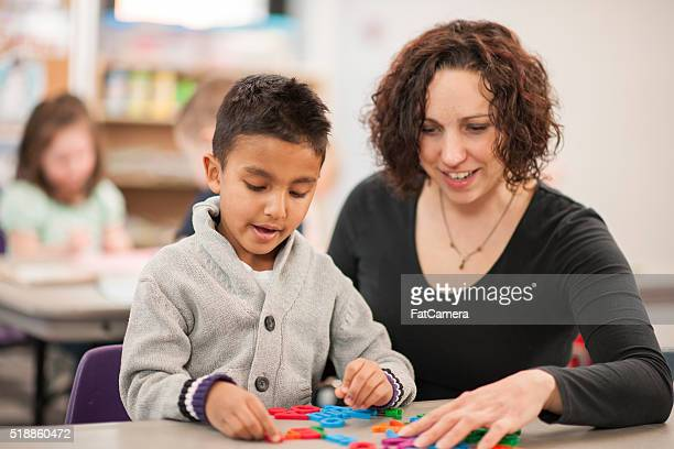 Teacher Helping a Student Learn to Spell