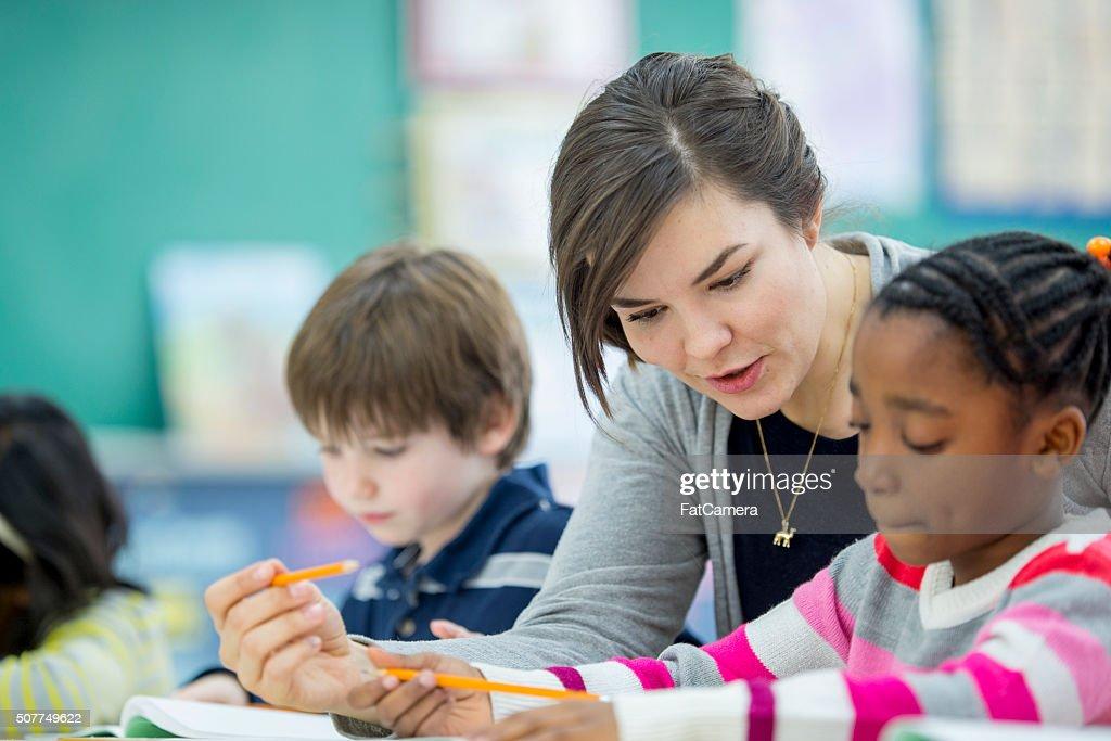 Teacher Helping a Student Understand an Assignment : Stock Photo