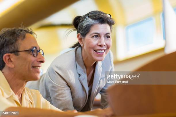 Teacher helping adult student use computer in library