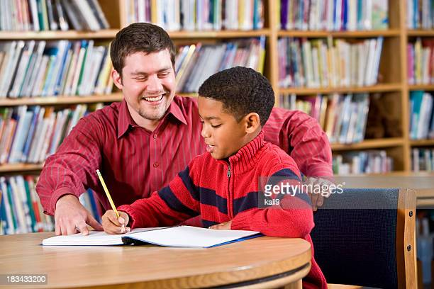 Enseignant aidant étudiant afro-américain à l'école, à la bibliothèque