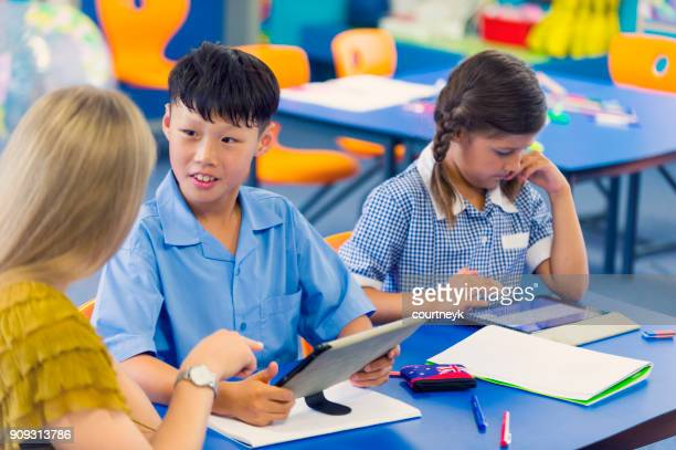 teacher helping an asian student in class. - uniform stock pictures, royalty-free photos & images