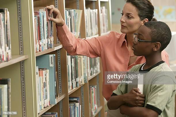 teacher helping boy choose a book - bibliothekar stock-fotos und bilder