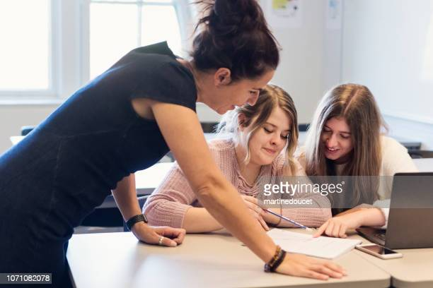Teacher helping College students working in team in classroom.