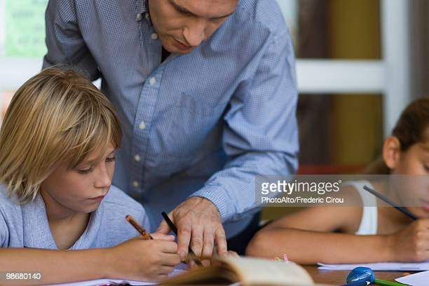teacher helping elementary school student in class - teacher bending over stock photos and pictures