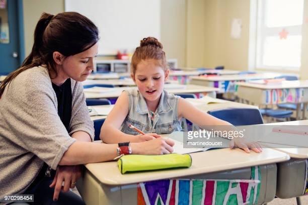 Teacher helping elementary student after class.