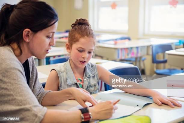 Lehrer helfen Grundschule Schüler nach dem Unterricht.