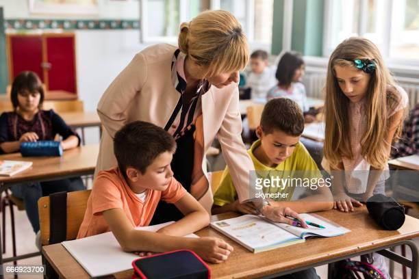 Lehrer helfen, Grundschüler mit Zuordnung im Klassenzimmer.
