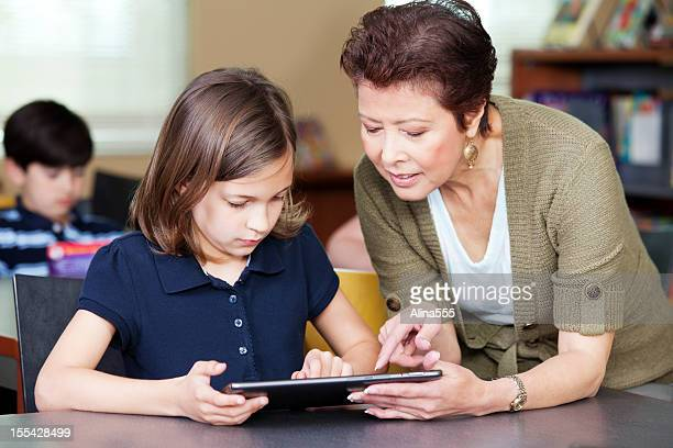 teacher helping elementary students with project on digital tablet - alina stock pictures, royalty-free photos & images