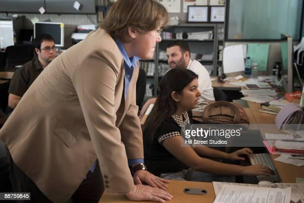 Teacher helping journalism student in classroom