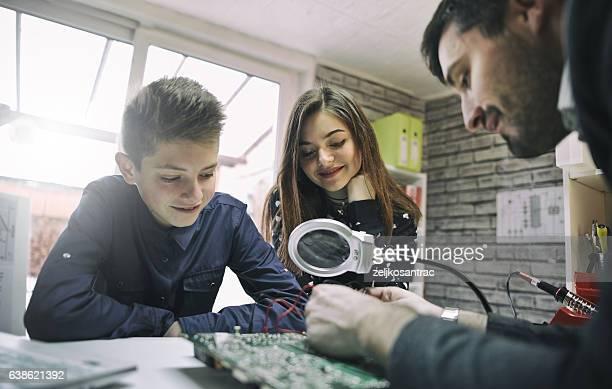 Teacher Helping kids  In electronic  Class