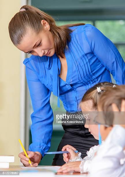 Teacher helping little schoolgirl