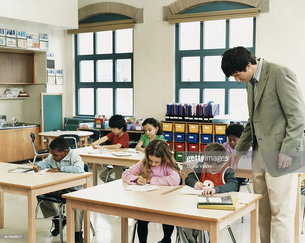 Teacher Helping Primary Schoolboys and Girls Studying in a Classroom : Stock Photo