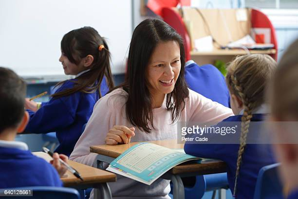 teacher helping pupil in classroom - teacher stock pictures, royalty-free photos & images