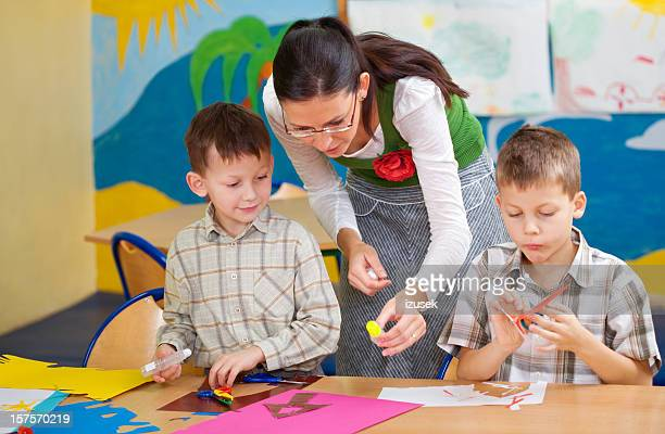 teacher helping pupils with artwork - teacher bending over stock photos and pictures