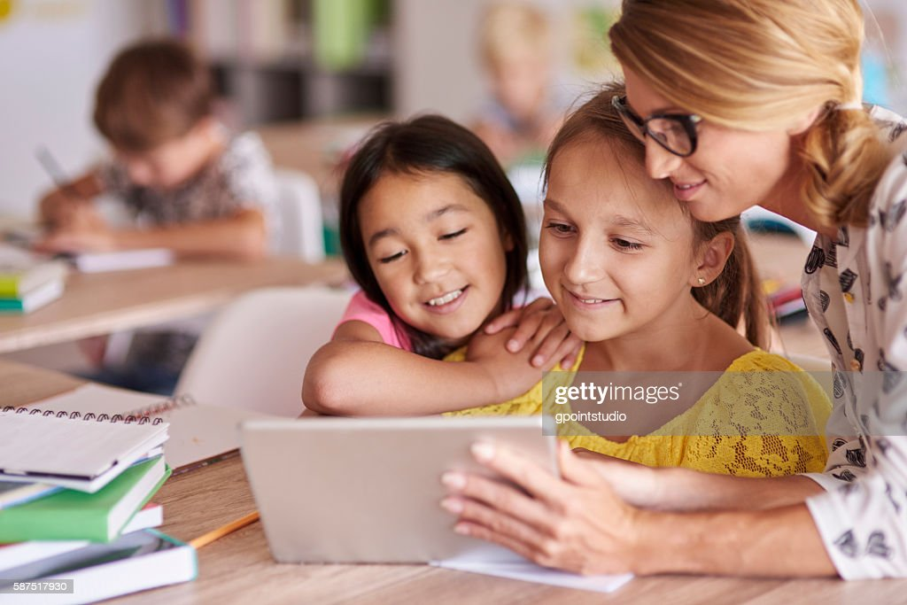 Teacher helping pupils with digital tablet : Stock Photo