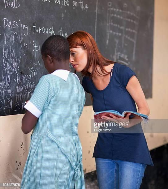 teacher helping school girl with her reading, kenya - hugh sitton stock-fotos und bilder