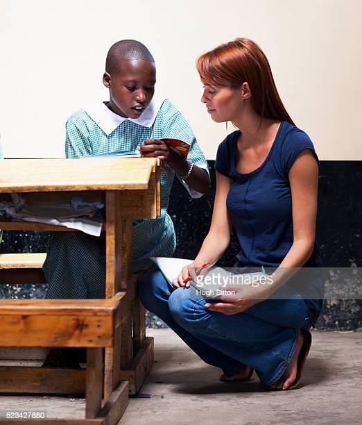 teacher helping school girl with her reading, kenya - hugh sitton - fotografias e filmes do acervo
