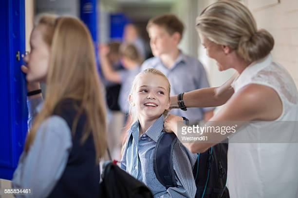 Teacher helping schoolgirl with backpack on hallway