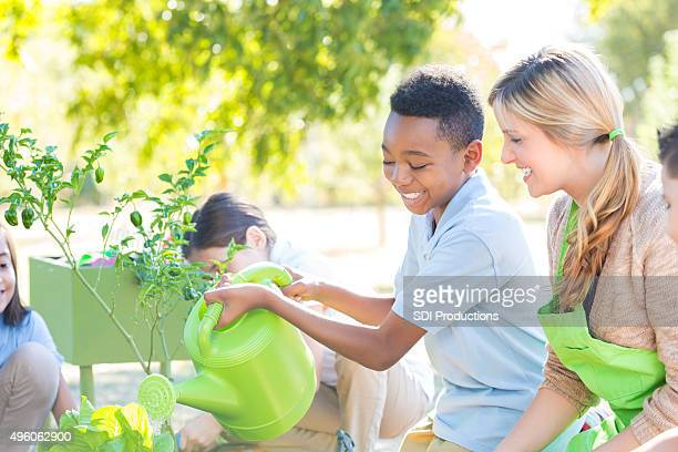 Teacher helping student plant vegetables in garden during science class