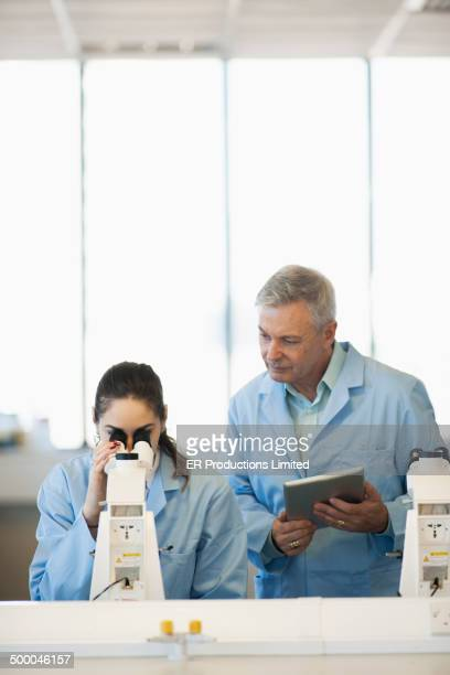 Teacher helping student use microscope in lab