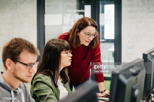 teacher helping student with computer work - education stock pictures, royalty-free photos & images