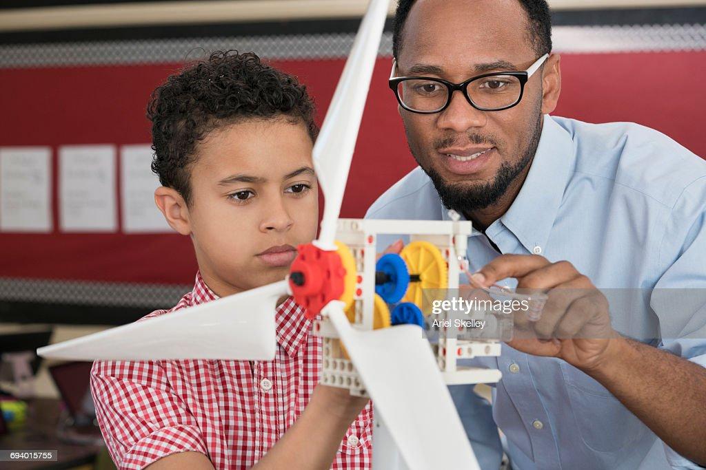 Teacher helping student with model wind turbine : Stock Photo
