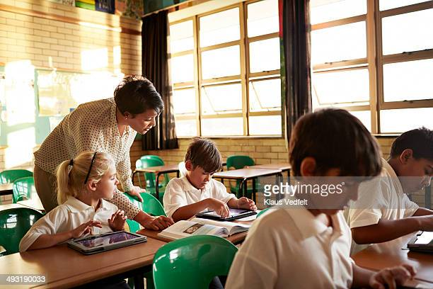 Teacher helping student with tablet in class