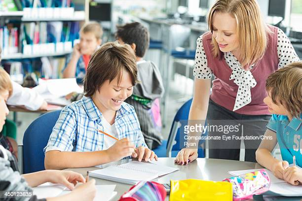 teacher helping student with work in classroom - human age stock pictures, royalty-free photos & images