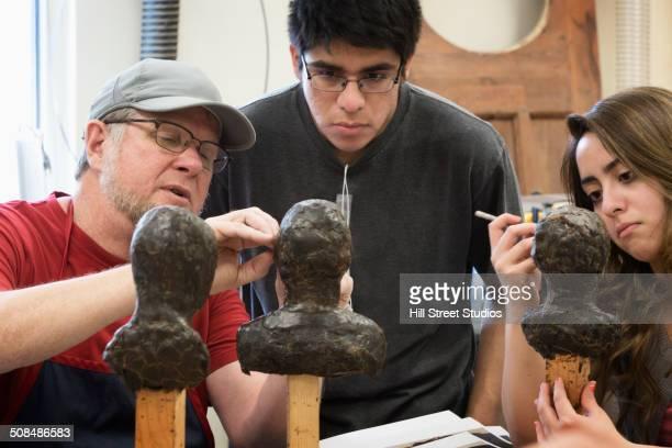 teacher helping students carve wax figures in class - lehm mineral stock-fotos und bilder