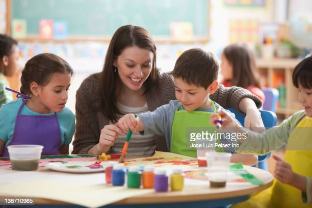 Teacher helping students in art class