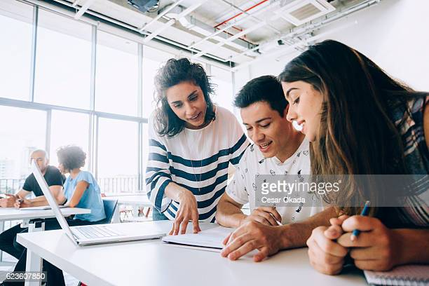 teacher helping students - studerende stockfoto's en -beelden
