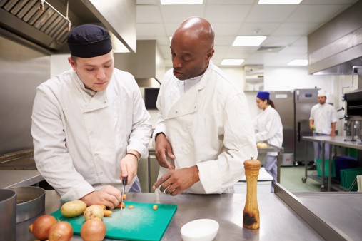 Teacher Helping Students Training To Work In Catering 511773173