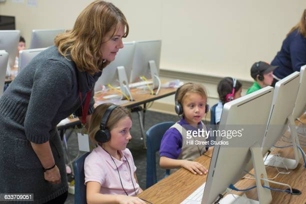Teacher helping students use computers in classroom
