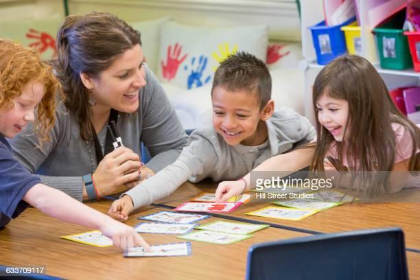 teacher helping students with project in classroom - educazione di scuola materna foto e immagini stock