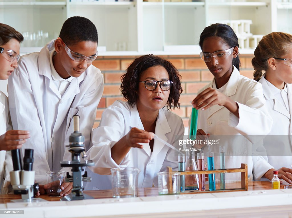 Teacher helping students with test tubes & pipette : Stock Photo