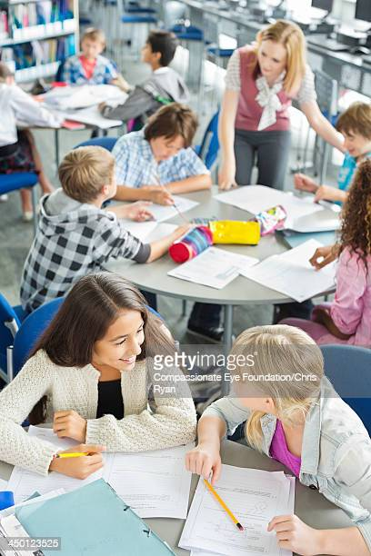 Teacher helping students with work in classroom