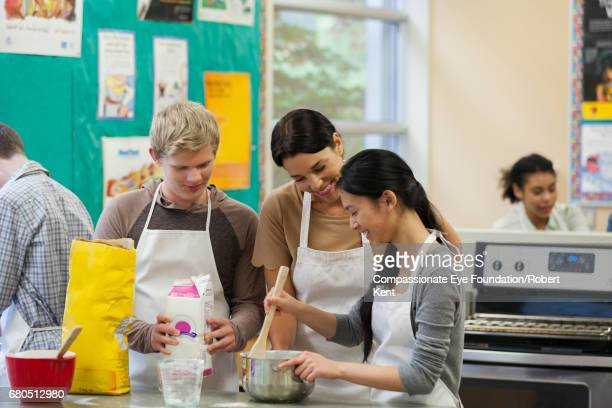 Teacher helping teenage students in cookery class