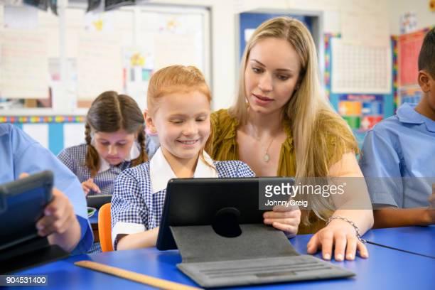 先生の教室でデジタル タブレットを使用して少女を助ける