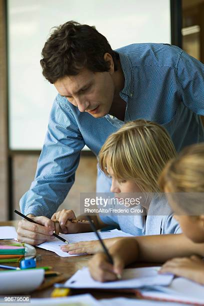 teacher helping young students with classwork - teacher bending over stock photos and pictures