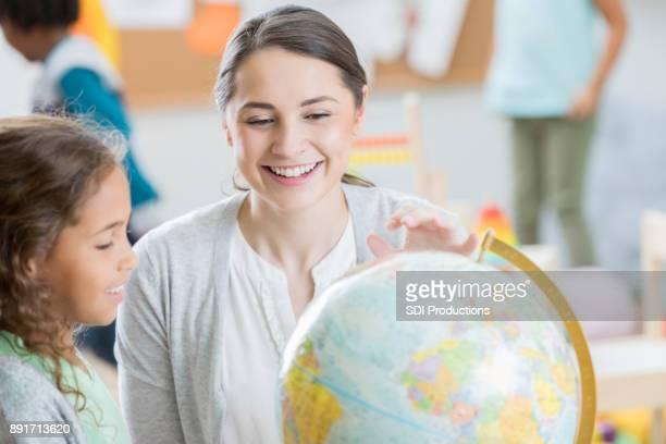 Lehrer hilft elementare Studenten mit Geographie Zuordnung