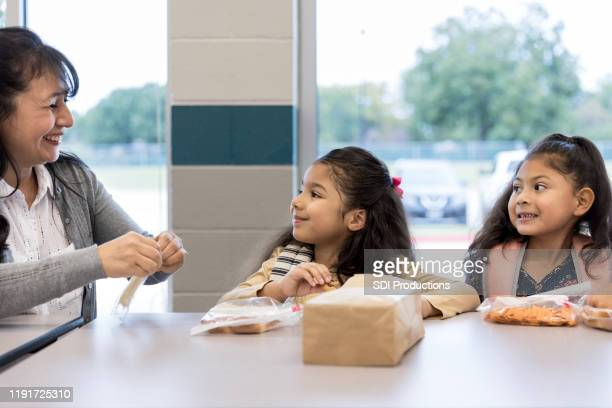 teacher helps elementary students during lunch - lunch bag stock pictures, royalty-free photos & images