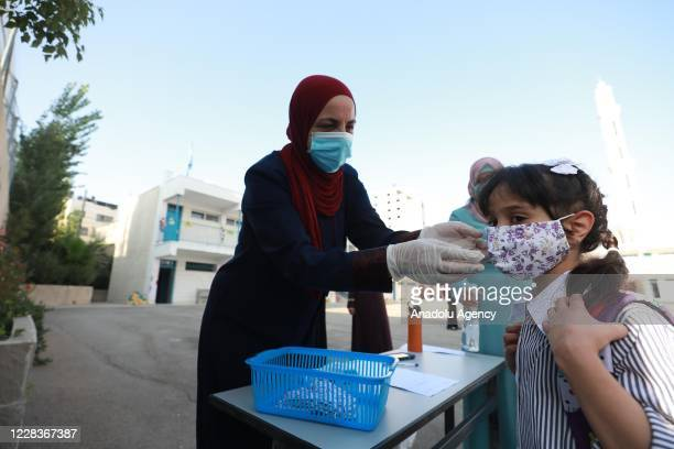 Teacher helps for a student to wear a mask ahead of a class after Palestinian students return to schools which have been closed due to the novel...