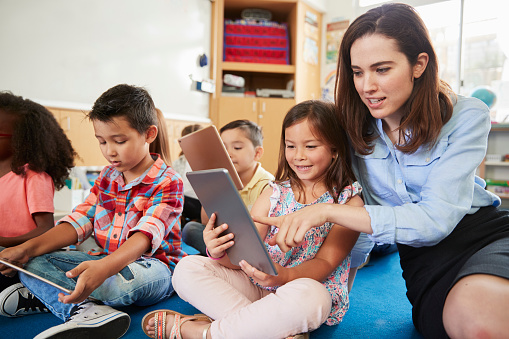 Teacher helps girl in elementary class with tablet computers 1031377560