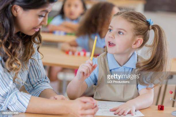 teacher helps young schoolgirl - spelling stock pictures, royalty-free photos & images