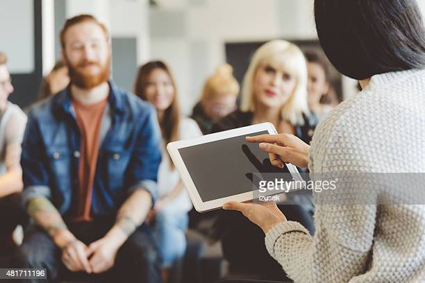 Teacher holding a digital tablet against auditorium
