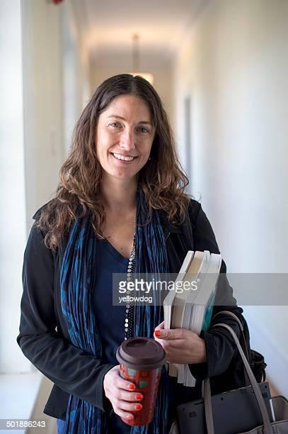 Teacher holding books and coffee, portrait
