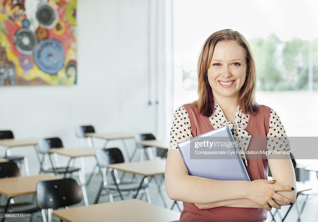 Teacher holding digital tablet in classroom : Stock Photo
