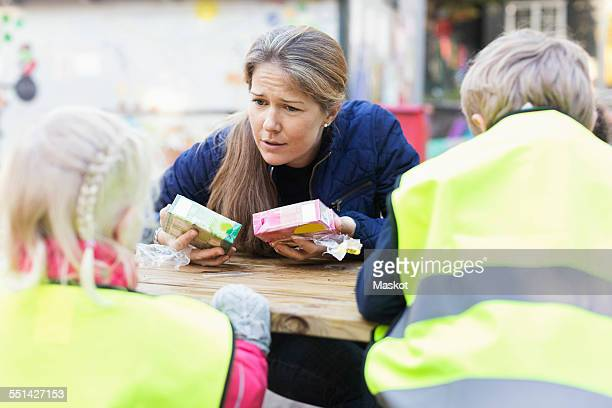 Teacher holding juice boxes while communicating with children outside kindergarten
